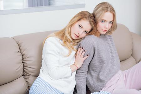 Zwei Freundinnen sitzen in Hauskleidung zusammen auf dem Sofa zu Hause.