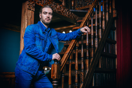 A portrait of a handsome man near the stairs. Beauty, casual denim fashion.