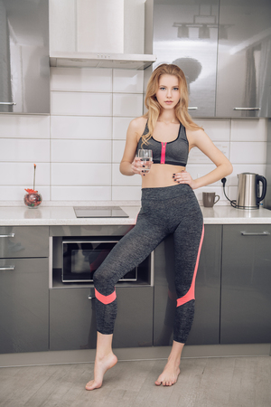 Portrait of a beautiful sexy girl in jogging suit at the kitchen in home. Fitness at home. Beauty, fashion.