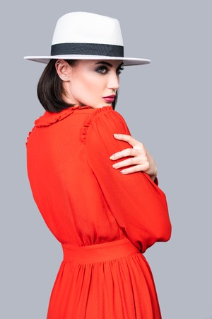 A portrait of a beautiful woman wearing a hat posing over the grey backgroung in the studio. Fashion, style, beauty.