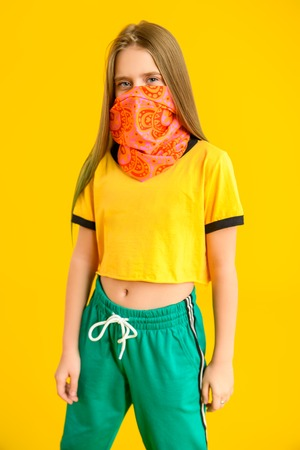 A portrait of a young girl posing in the studio over the yellow background. Sport fashion for teenagers.
