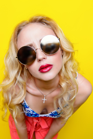 Attractive young woman wearing bright clothes and sunglasses over yellow background. Bright style, fashion. Optics style. Stock Photo