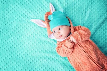 Ein Nahaufnahmeporträt eines lustigen Babys, das einen Hut und einen Overall eines Hasen trägt. Familie, Elternschaft. Waren für Neugeborene. Standard-Bild
