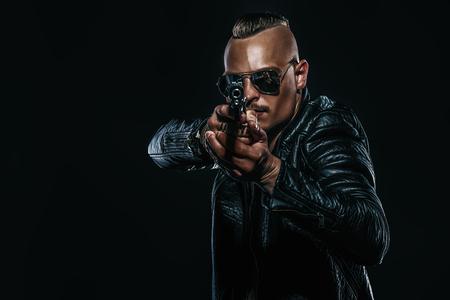 Dunkles Porträt eines ernsten Gangstermannes mit der Waffe, die schwarze Lederjacke trägt.