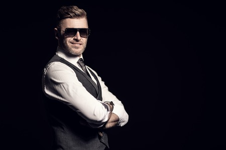 A portrait of a handsome brutal mature man posing in the studio over the black background. Casual formal fashion, men's beauty.