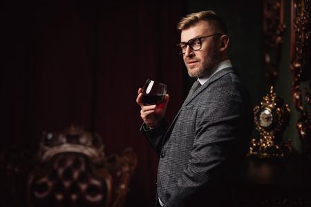 Un ritratto di un bell'uomo maturo in un costume formale che beve vino. La bellezza maschile, la moda. Archivio Fotografico
