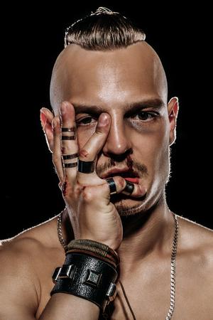 Fight club, MMA. Portrait d'un combattant de méchant avec un visage dans le sang, démontrant ses muscles et sa force. Rocker, punk.