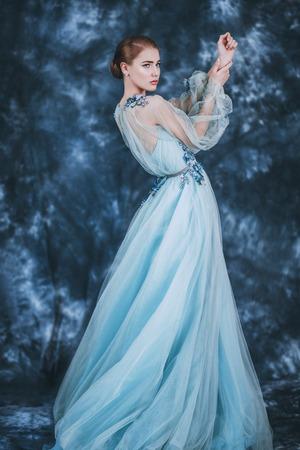 Un portrait en pied d'une mystérieuse dame vêtue d'une robe duveteuse posant à l'intérieur. Conte de fées, mode.