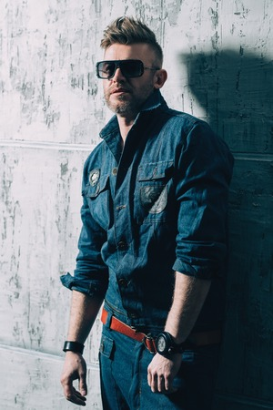 A portrait of a handsome brutal mature man posing in the studio over the grey wall. Casual denim fashion, men's beauty. Stock Photo - 120121616