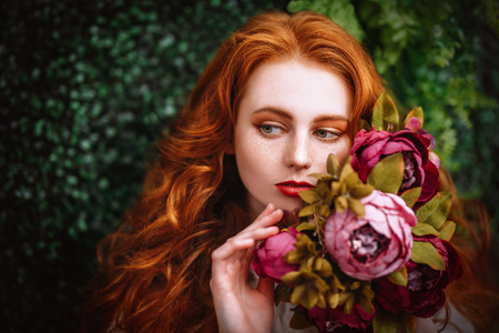 A close up portrait of a lovely mysterious girl with roses. Beauty, cosmetics. Stock Photo - 120121625