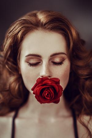 Ein Nahaufnahmeporträt eines reizenden mysteriösen Mädchens mit einer roten Rose. Schönheit, Kosmetik. Standard-Bild