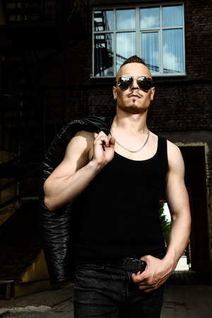 Portrait of a punk man in the street. Guy in the backyard. Fashion, subculture. Stock Photo