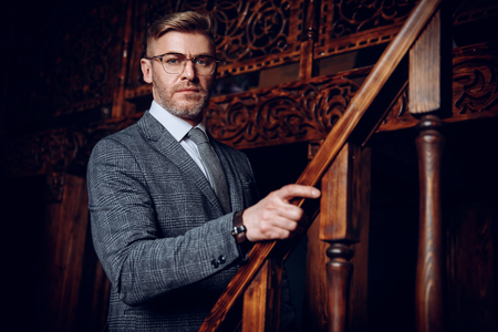 A portrait of a handsome mature man in a formal costume posing on the stairs. Men's beauty, fashion.