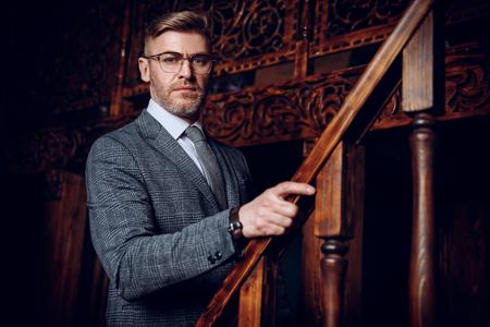 Un retrato de un apuesto hombre maduro con un traje formal posando en las escaleras. Belleza masculina, moda.