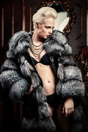 Porträt einer schönen Frau im luxuriösen Pelzmantel, der im Innenraum aufwirft. Luxus, reicher Lebensstil. Modeschuss.