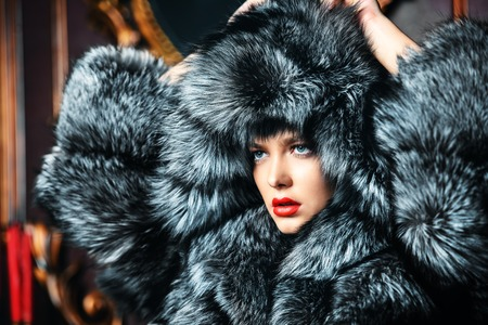 Portrait of a beautiful woman in luxurious fur coat posing in interior. Luxury, rich lifestyle. Fashion shot. 스톡 콘텐츠