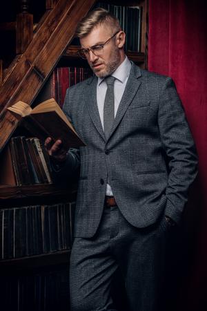 Un ritratto di un bell'uomo maturo in un costume formale che legge un libro. La bellezza maschile, la moda. Archivio Fotografico