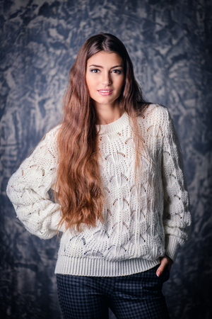 A portrait of beautiful Lady in a white sweater over the grunge background. Natural pure beauty. Make-up concept.