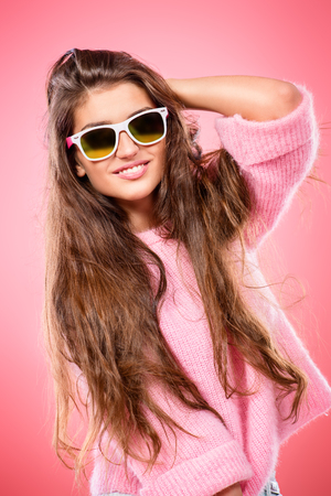 A portrait of a beautiful and cute young lady posing over pink background. Fashion concept.