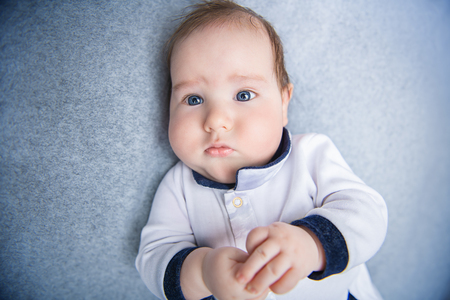A portrait of a beautiful baby lying in the bed. Family, parenthood. Goods for newborns. Stock Photo