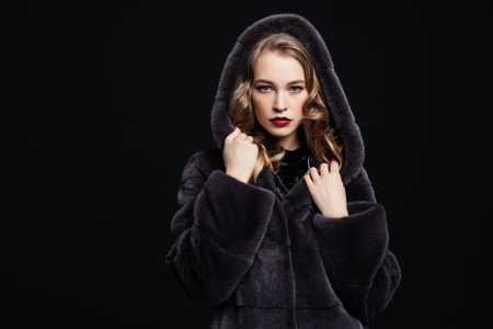 A portrait of a beautiful woman wearing a fur coat with a hood. Beauty, winter fashion, style.