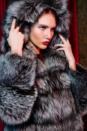 Bliska portret pięknej kobiety w futrze z kapturem. Uroda, moda zimowa, styl. Zdjęcie Seryjne