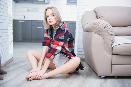 Portrait of a beautiful girl sitting in casual clothes on the floor near the sofa in the room. Beauty, cosmetics. Home shot.