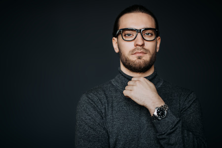 A portrait of a handsome man wearing casual clothes and glasses posing in the studio. Mens beauty, casual fashion.