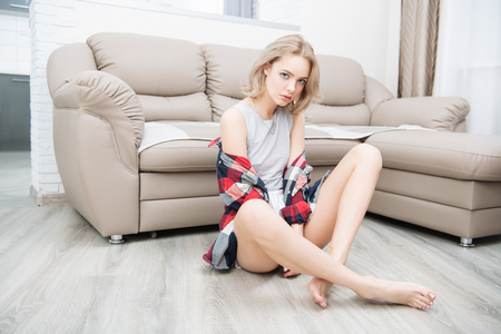 Portrait of a beautiful sexy girl sitting in casual clothes on the floor near the sofa in the room. Beauty, cosmetics. Home shot. Stock Photo