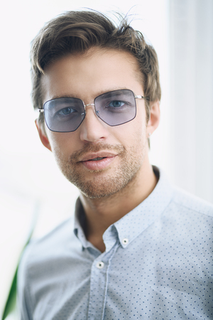 A close up portrait of a handsome man in sunglasses over the white background. Beauty, fashion for men. Foto de archivo