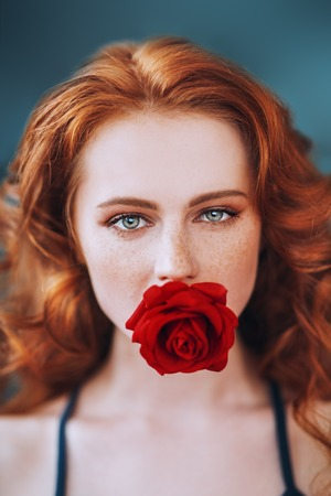 A close up portrait of a lovely mysterious girl with a red rose. Beauty, cosmetics. Stock Photo - 120796188