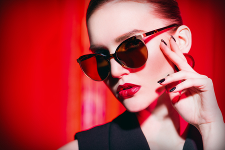 A close up portrait of a confident lady wearing sunglasses. Beauty, make-up, style.
