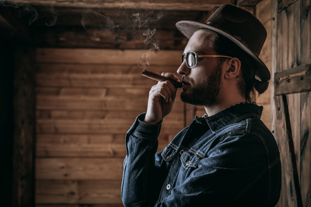 A portrait of a handsome man standing in front of the wooden house and smoking a cigar. Beauty, casual fashion.