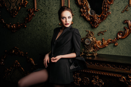 A portrait of a beautiful sexy woman wearing a black blazer and posing in classic interior. Fashion, style, beauty, interior.