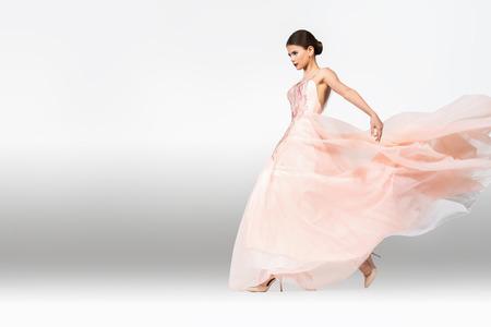 Ein Porträt in voller Länge einer charmanten Dame in einem Hochzeitskleid, die im Studio posiert. Hochzeitsmode, Braut. Standard-Bild