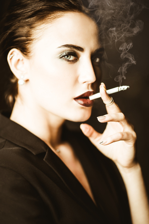 A portrait of a beautiful woman wearing a black blazer and smoking a cigarette. Fashion, style, beauty.