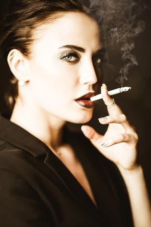Un retrato de una bella mujer vestida con una chaqueta negra y fumando un cigarrillo. Moda, estilo, belleza.