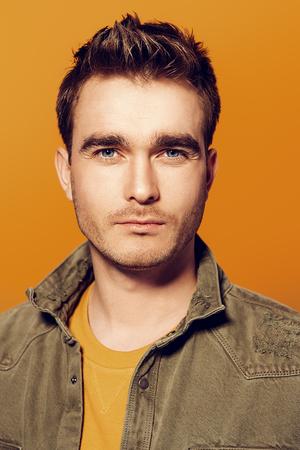 Een close-up portret van een knappe jonge man die zich voordeed in de studio op de gele achtergrond. Schoonheid, stijl.