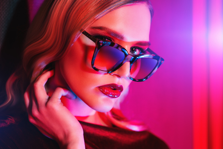 Een close-up portret van een zelfverzekerde dame die een bril draagt. Schoonheid, make-up, stijl. Stockfoto