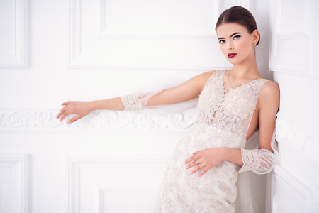A portrait of a charming lady in a wedding dress posing in the studio. Wedding fashion, bride. Foto de archivo