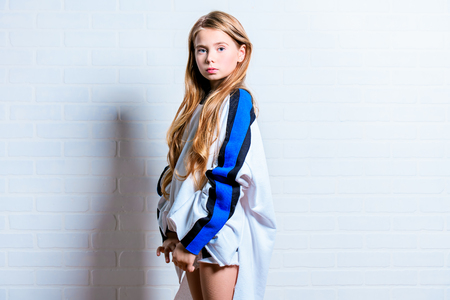 A portrait of a cute emotional girl posing over the white wall of bricks. Beauty, fashion for kids and teenagers.