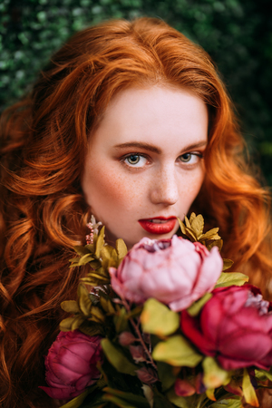 A close up portrait of a lovely mysterious girl with roses. Beauty, cosmetics.