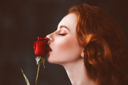 A close up portrait of a lovely mysterious girl with a red rose. Beauty, cosmetics. Stock Photo - 126422505