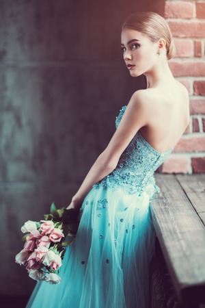 A portrait of a mysterious lady in a fluffy dress posing indoor with flowers. Fairy tale, fashion.