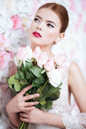 A close up portrait of a dreamy lady in a wedding dress posing indoor with flowers. Wedding, beauty, fashion.