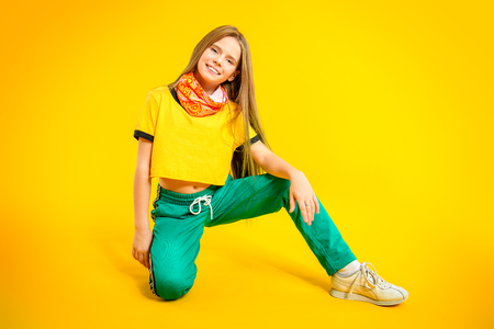A full length portrait of a young active girl posing in the studio. Sport fashion for teenagers.