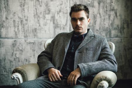 Een portret van een modieuze jonge man die zich voordeed in de fauteuil over de grijze achtergrond. Formele mode voor mannen.