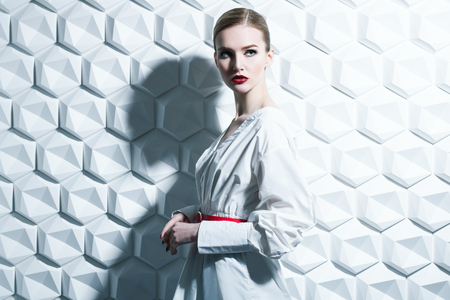 A portrait of a confident lady wearing a white dress and posing in the studio over the white background. Beauty, make-up, style.