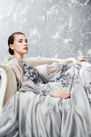 A portrait of a charming lady in a silver dress posing on the chair. Fairy tale, fashion.