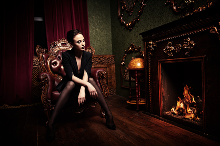 A full length portrait of a beautiful woman wearing a black blazer and posing in classic interior on the armchair. Fashion, style, beauty, interior.